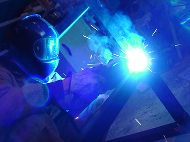 Trettel Design Build employee is lit up by the glow of MIG welding custom furniture steel frame wearing protective helmet and gear in their fabrication shop