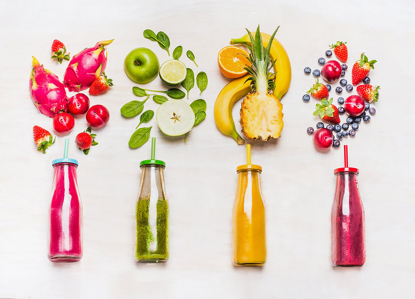 Assortment of fruit  and vegetables smoothies in glass bottles with straws on white wooden