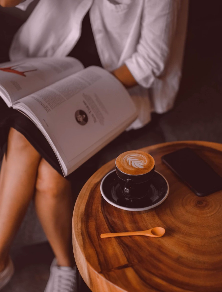 woman holding a book, next to a coffee mug