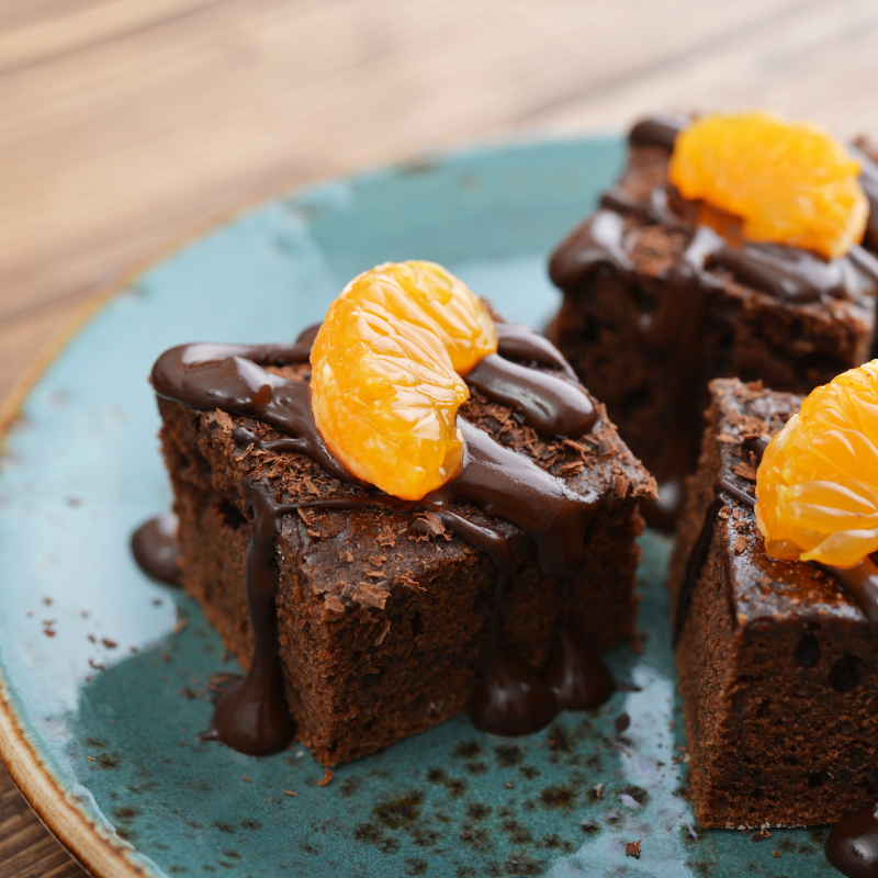 three chocolate brownies on a teal plate with chocolate drizzle and tangerine slices on top