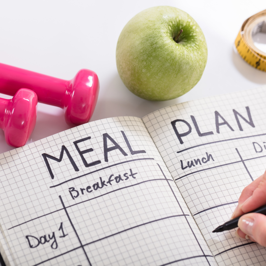 "image of someone writing in notebook with words ""meal plan."" pink weights and green apple in image."