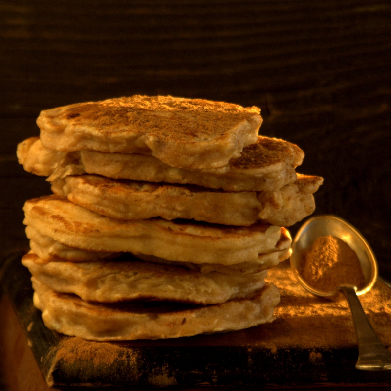 a stack of pancakes next to a spoon with cinnamon powder in it.