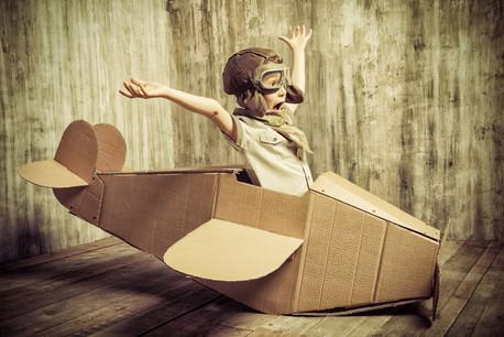 Cute dreamer boy playing with a cardboar