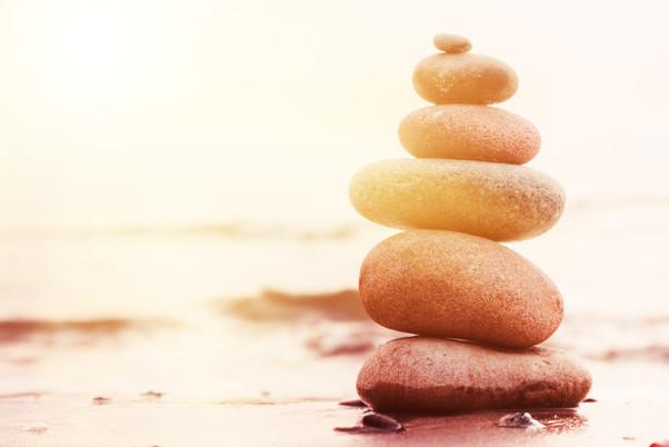Stones pyramid on sand symbolizing zen,