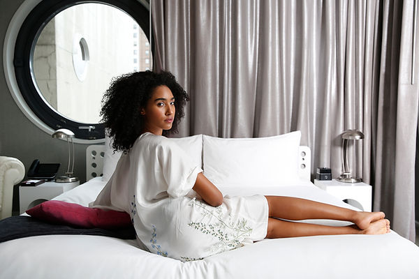 "<img src=""girl reclining.png"" alt="" Girl of mixed race with an afro wears white dress. she reclines on the bed in front of a large circular window with grey curtains, at the dream down town hotel"">"