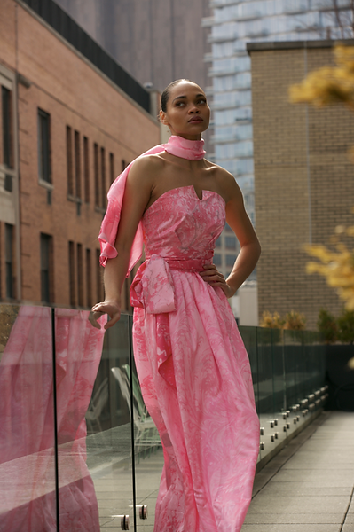 "<img src=""Long Pink satin Dress.png"" alt=""model wearing a pink marbled dress with a scarf and belt in a new york balcony and posing"">"