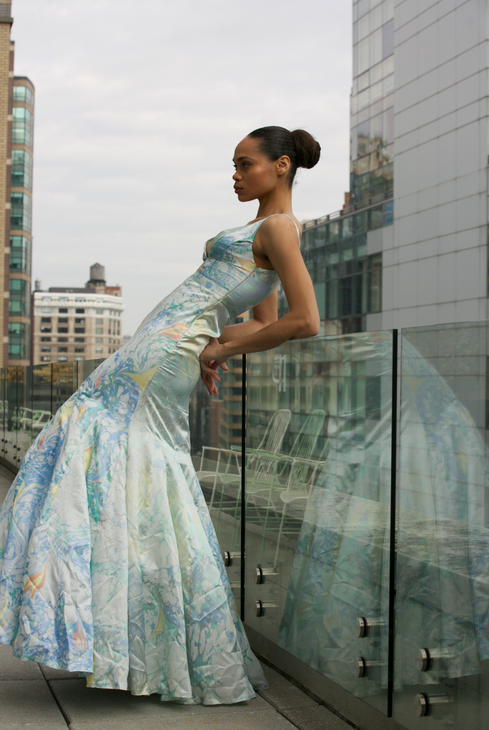 "<img src=""Long flared Dress.png"" alt=""Model leans at the balcony wearing a long flared dress with marbled designs"">"