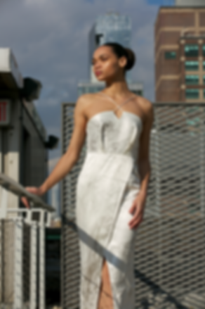 """<img src=""""Front slit dress .png"""" alt="""" Model wears a white slit dress in marbled grey and white and poses on a rooftop in manhattan"""">"""