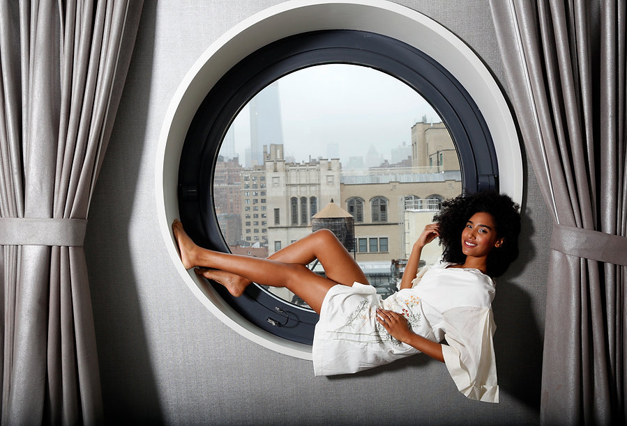 "<img src=""girl reclining.png"" alt="" Girl of mixed race with an afro wears white dress. she reclines in front of a large circular window with grey curtains at the dream down town hotel"">"