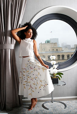 "<img src=""embroidered dress on girl.png"" alt="" Girl of mixed race with an afro wears white top and embroidered long skirt with flowers and leaves, she poses in front of a large circular window at the dream down town hotel"">"