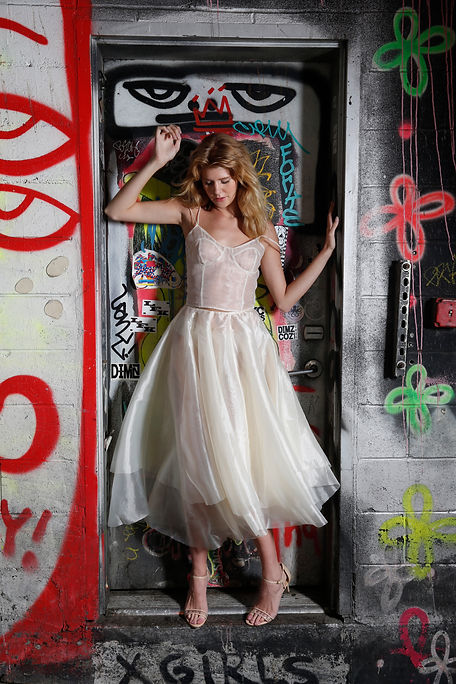 "<img src=""sheer dress.png"" alt="" white model poses with a sheer organza dress against a colorful graffiti background"">"