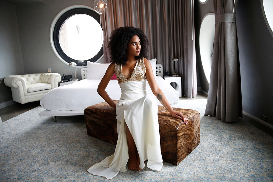"""<img src=""""white long dress.png"""" alt="""" Girl with Afro is wearing a gold embroidered plunging neckline dress and sits in a hotel room with white furniture grey curtains and large circular windows"""">"""