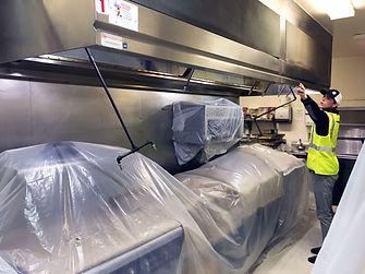 Bare Metal Standard employee inspecting hood duct.
