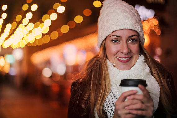 smiling-woman-in-city-warming-hands-with