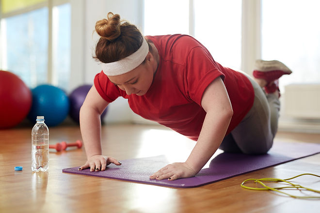 Portrait of young obese woman working out on yoga mat in sunlit fitness studio_ performing knee push