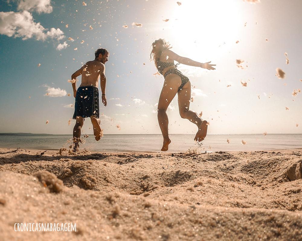casal correndo na areia