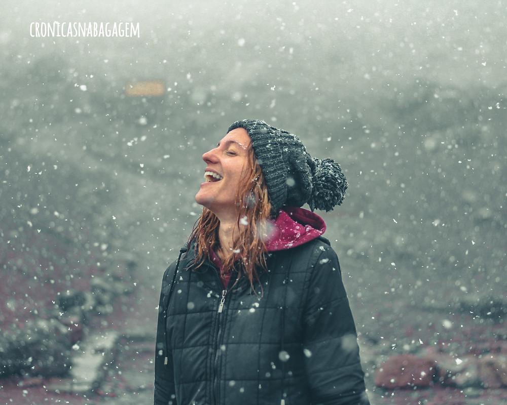 mulher rindo sob a neve