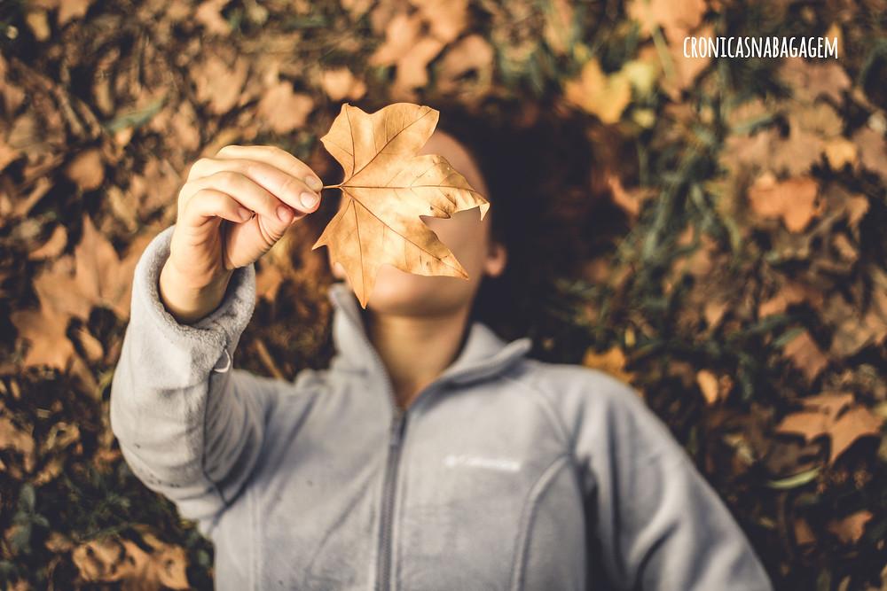 mulher deitada no chão com folhas de outono