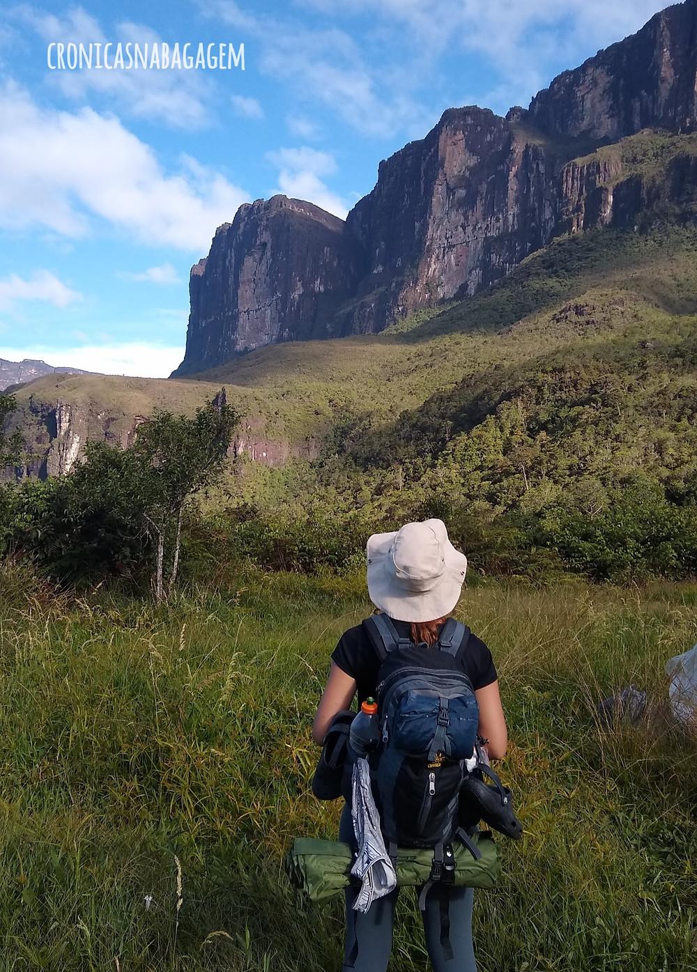 Mulher com mochila nas costas olhando para o Monte Roraima
