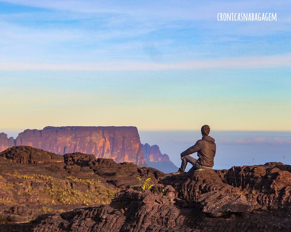 Homem sentado contemplando o amanhecer no topo do Monte Roraima