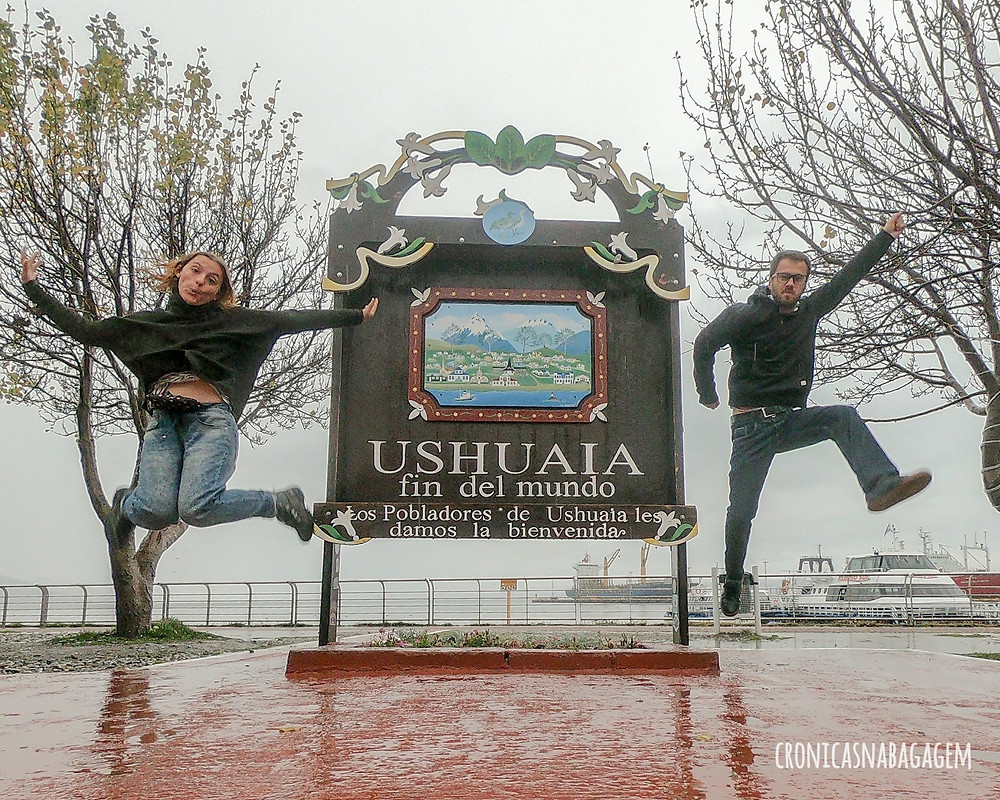 casal em frente a placa de Fim do Mundo, Ushuaia