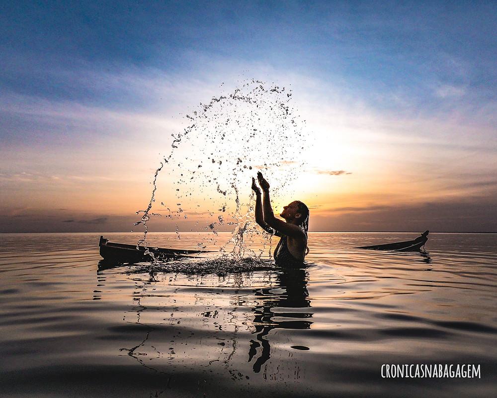 mulher jogando água para cima no rio com pôr do sol ao fundo