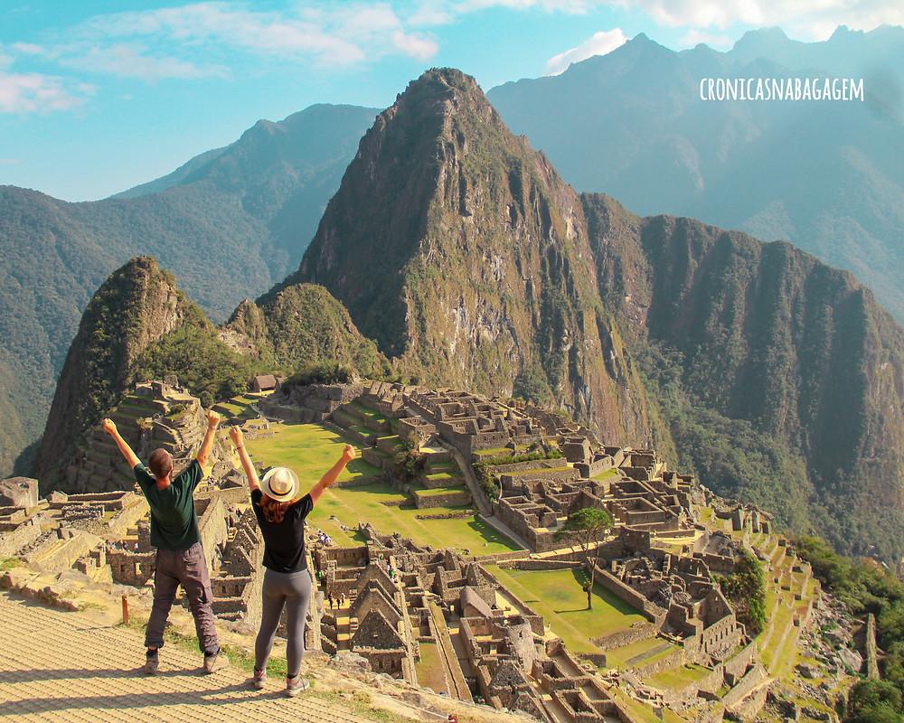 casal de braços levantados em Machu Picchu, Peru