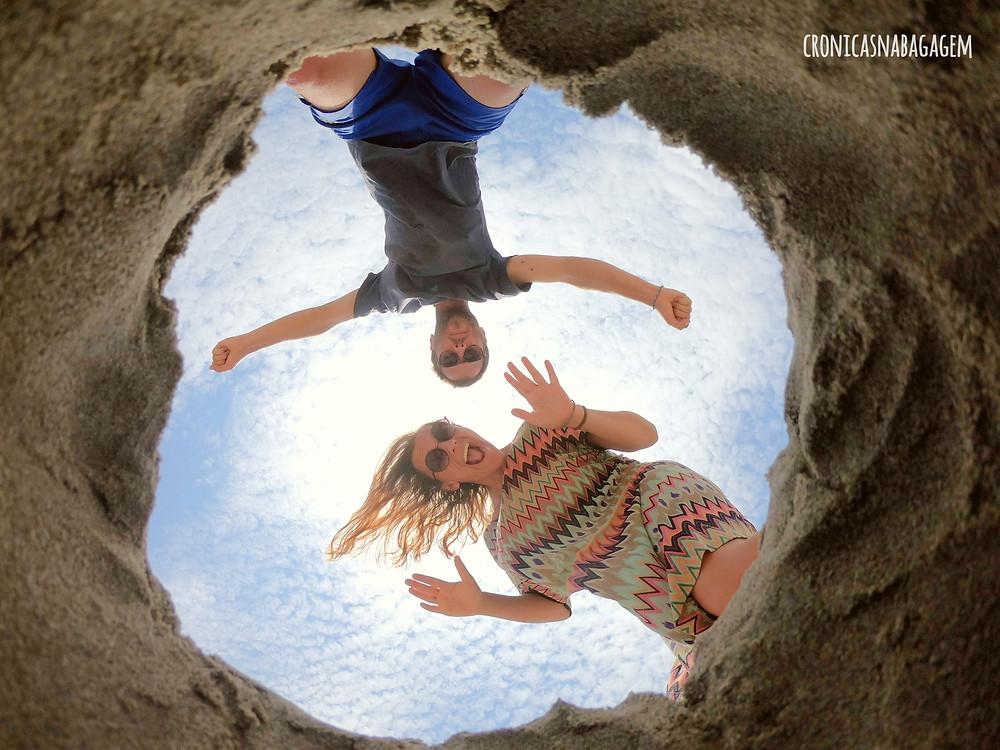 casal olhando para buraco na areia