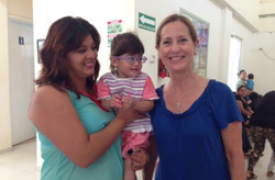 Julie Murray poses for a photo with a local mother and child waiting to be seen