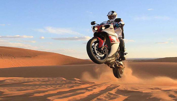 a street motorcycle raising hell in the desert sand