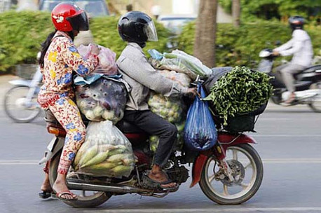a motorcycle ridiculously packed with people and groceries