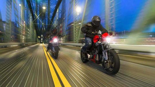 a beautiful night photo of motorcycles crossing a bridge
