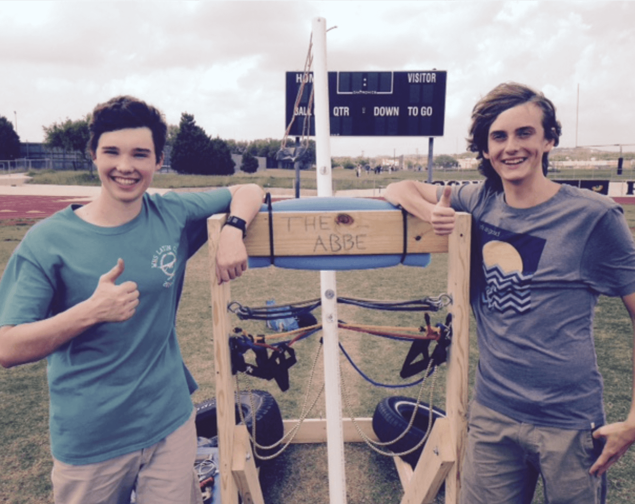 Two club members proudly pose in front of a catapult named after Magister Abbe.