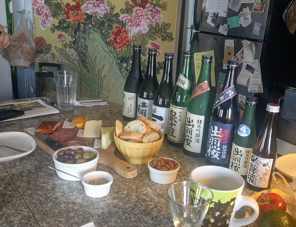 Avariety of Sake bottles presented with bread, nuts, cured meats, and cheeses