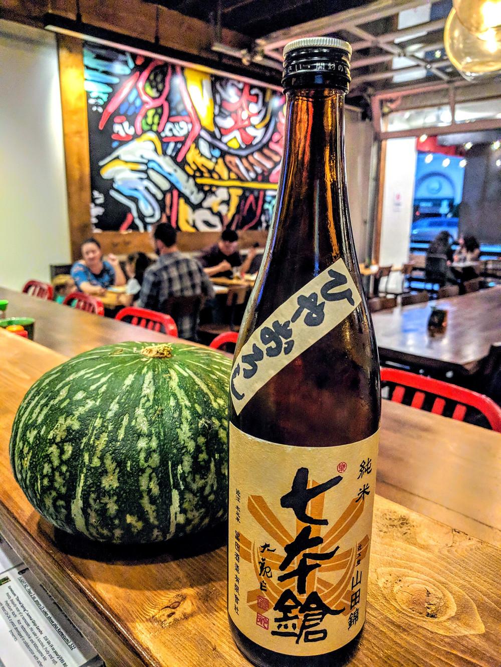 Bottle of Shichi Hon Yari Autumn Seasonal Sake with Kabocha Pumpkin at a Japanese Restaurant