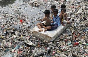 These children ride their makeshift raft