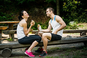 couple outdoors laughing and eating