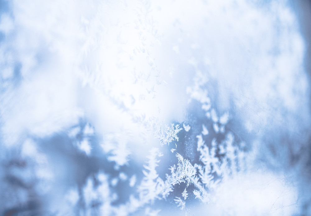 Image Description: A close up picture of frost. You can see the individual white snowflakes against the light blue surface.