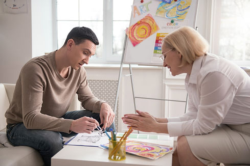 Bright colors. Merry mature psychologist sharing her observation while man drawing.jpg