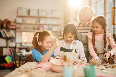 Portrait of female art teacher working with little girls in pottery class, scene lit by se