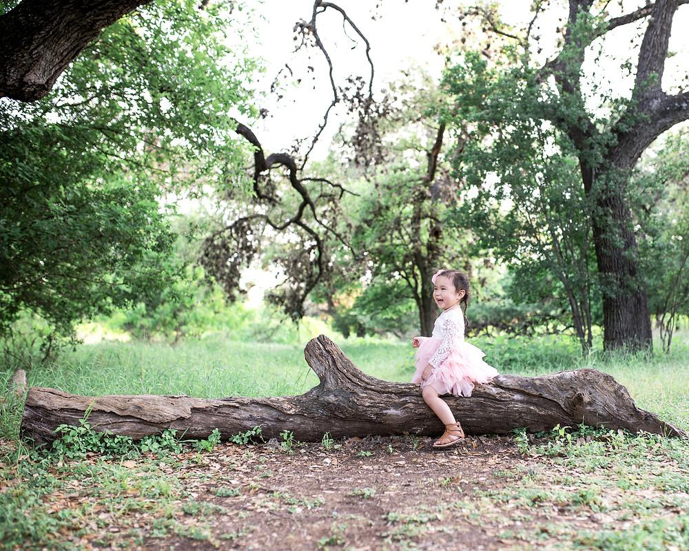 girl sitting on log