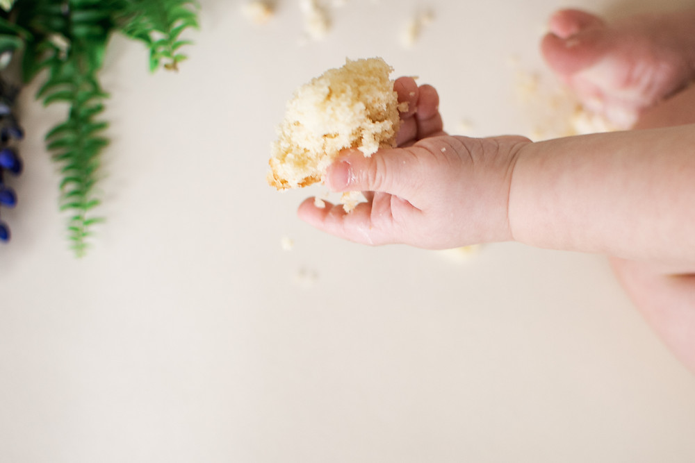 baby with cake in hand