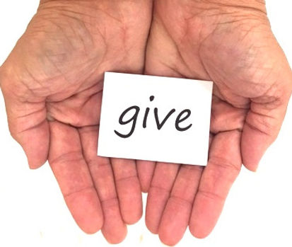 hands holding a card that says give