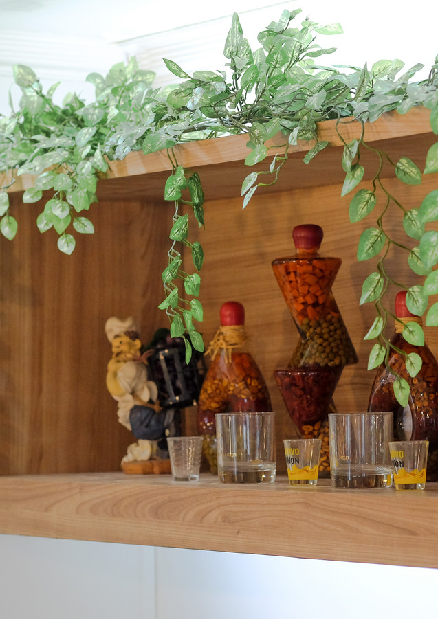 Our hanging shelf, garnished with beverages and greens, is the centerpiece of our French Garden Themed Restaurant.
