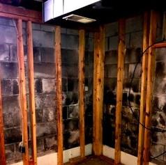 Behind basement drywall.