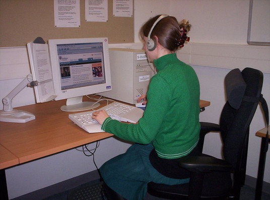 Young adult working on a computer with accessible keyboard