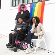 Disabled BIPOC in front of pride flag