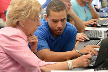 Older and younger adult working together on laptop