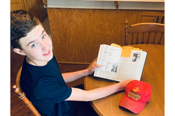 Gunner B. reading about Survivor Edgar Harrell from his favorite book, Only 316 Survived