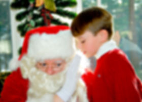 Boy whispering into santa's ear